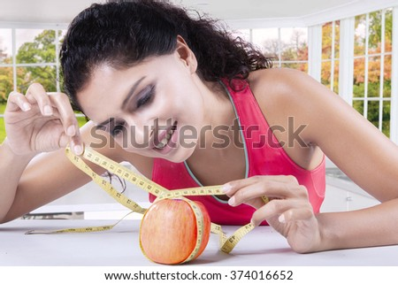 Beautiful indian woman measure a red apple with a measuring tape in the kitchen - stock photo