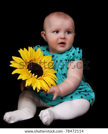 beautiful infant girl in polka dot dress sitting with large golden sunflower. isolated on black - stock photo