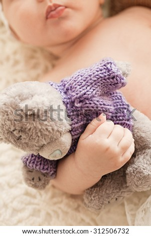 Beautiful innocent newborn sleeping. Adorable little girl holding close to him his bear toy - stock photo