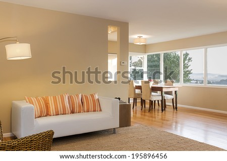 Beautiful interior of med century home with large view window, dining area, sofa in white and orange pillows framed by modern light and wooden stand. - stock photo