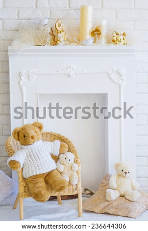 Beautiful interior with chair, decorative fireplace and teddy bears - stock photo