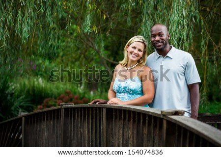 Beautiful interracial couple portrait at a park in summer standing on a bridge