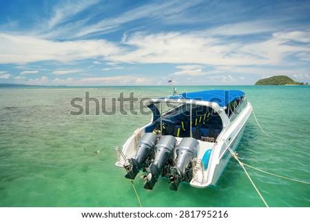 Beautiful island beach with motor boat - stock photo