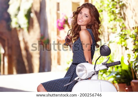 beautiful italian woman sitting on a italian scooter.  - stock photo