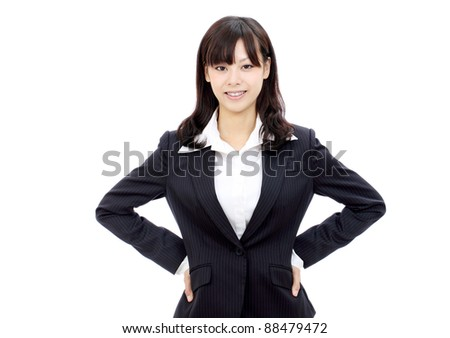 Beautiful japanese businesswoman standing with hands on hips - stock photo