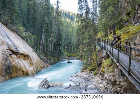 Beautiful Johnston Canyon walkway with turquoise water below, in Banff National Park, Alberta, Canada.  Shot with long exposure to give colorful river a smooth & dreamy effect. - stock photo