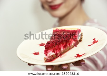 Beautiful joyful woman posing with the piece of cheesecake with raspberries. Sweet food theme.