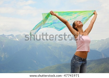 beautiful joyful woman with kerchief. she is looking at sky. mountains in background.