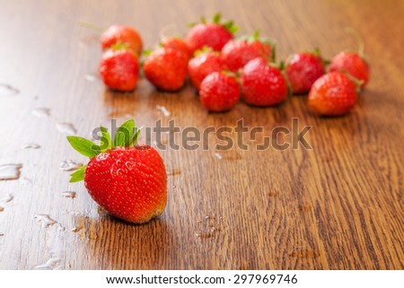 beautiful, juicy, ripe strawberry on a wooden surface. concept of leadership - stock photo