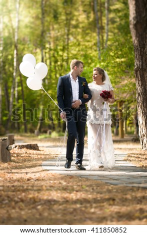 Beautiful just married couple with balloons walking at park