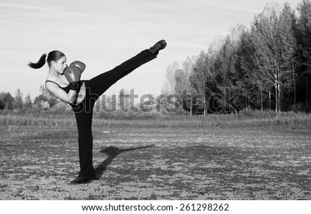 Beautiful kickboxing girl exercising outdoor at sunset. - stock photo