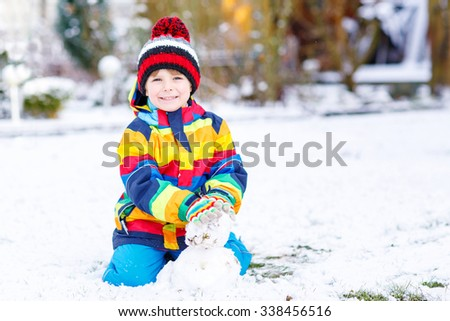 Beautiful kid boy in colorful clothes making a snowman, playing and having fun with snow, outdoors  on cold day. Active outdoors leisure with children in winter. - stock photo