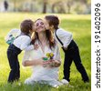 Beautiful kids and mom in spring park, flower and present. Mothers day celebration concept  - stock photo