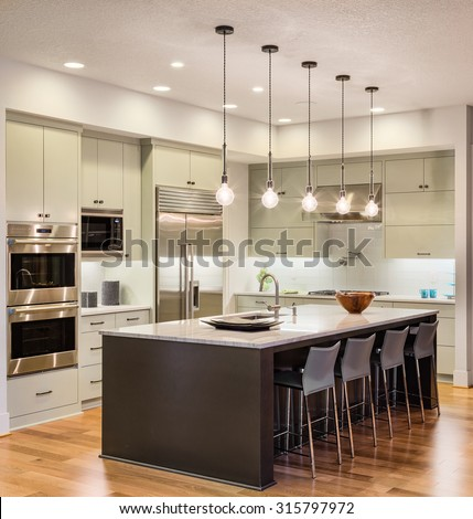 Beautiful kitchen interior in new luxury home with island, cabinets, pendant lights, stainless steel refrigerator, oven, microwave, and hardwood floors - stock photo