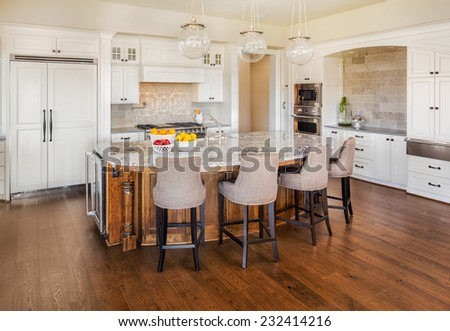 Beautiful Kitchen Interior in New Luxury Home with Island, Pendant Lights, Chairs, Hardwood Floors, Cabinets, and Oven/Range - stock photo