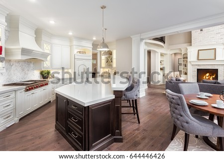 Beautiful kitchen interior in stunning new luxury home with dining room and view of living room with fireplace.  Spacious open floor plan design.