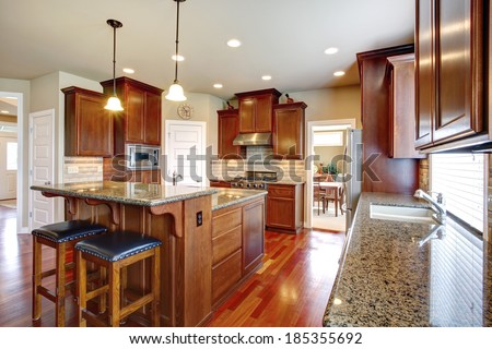 Beautiful kitchen room with oak cabinets, steel appliances. View bar counter with black chairs