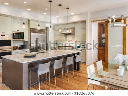 Beautiful Kitchen with Island, Sink, Dining Room Table, Stainless Steel Refrigerator, Pendant Lights, Microwave, Oven, Range, and Chairs in New Luxury Home   - stock photo