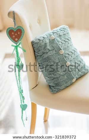 beautiful knitted pillow lying on the chair in the room. - stock photo