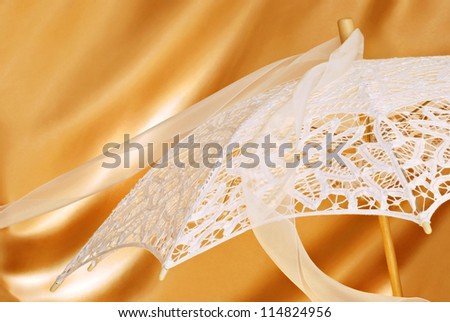 Beautiful lace parasol with chiffon ribbon on gold satin background with copy space.  Close-up with shallow dof.  Ideal for use as a bridal shower invitation. - stock photo