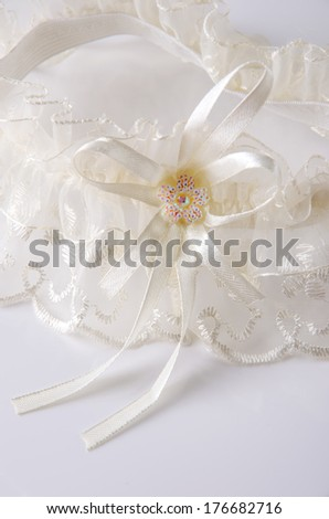 Beautiful lace wedding garter with a bow. - stock photo