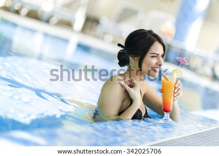 Beautiful lady drinking a cocktail in a swimming pool and relaxing - stock photo