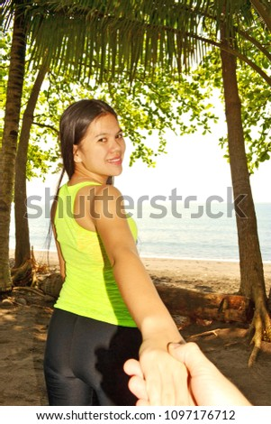 Beautiful lady in a tropical forest holding the hand of her lover to follow her to the beach