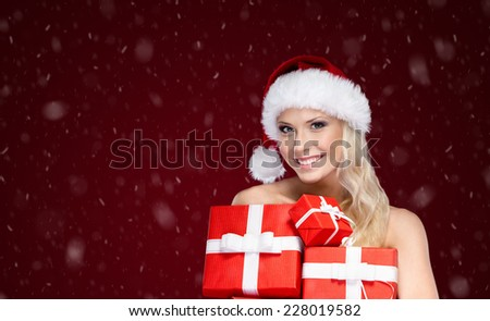 Beautiful lady in Christmas cap holds a set of gifts wrapped with red paper, isolated on purple - stock photo