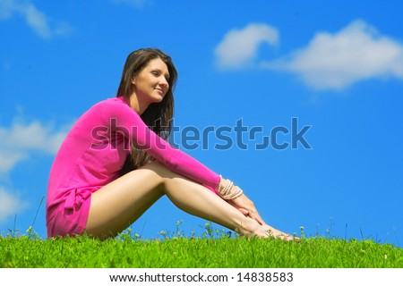 Beautiful lady in pink dress relaxing in the park
