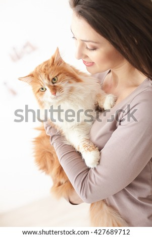 Beautiful lady is caring about her pet - stock photo