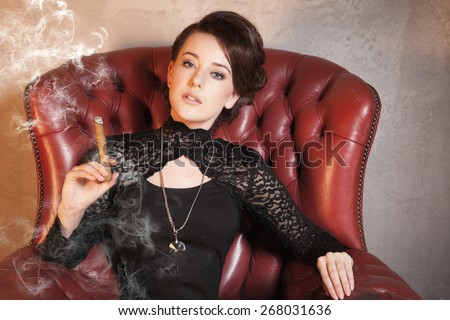 Beautiful lady is smoking cigar on stylish armchair - retro style - stock photo