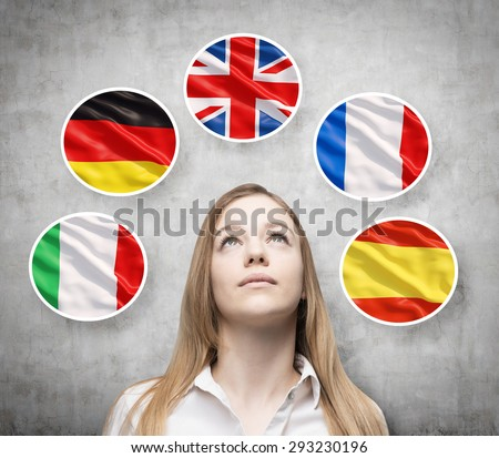 Beautiful lady is surrounded by bubbles with european countries' flags (Italian, German, Great Britain, French, Spanish). Learning of foreign languages concept. Concrete background. - stock photo