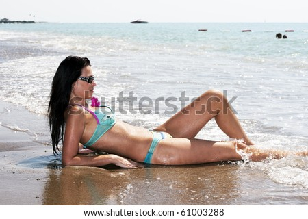 beautiful lady is touched by the waves leaving - stock photo