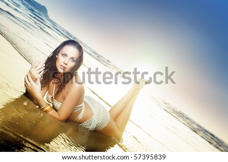 Beautiful lady laying at the ocean beach during summer sunset. Natural colors and lighting
