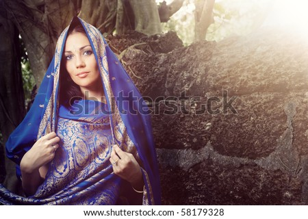 Beautiful lady outdoors in elegant sari near the old stony wall. Horizontal portrait - stock photo