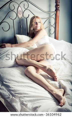 Beautiful lady relaxing in the bedroom - stock photo