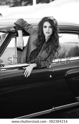 Beautiful lady sitting in a retro car. Black and white. Brunette hair style. Fashion portrait.