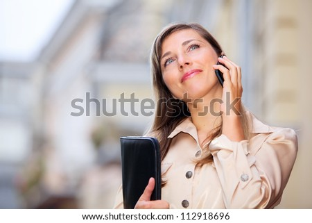 Beautiful lady using cellphone and holding folder with copy space - stock photo