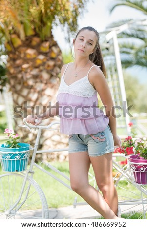 Beautiful lady wear a casual clothes and ride a fake decor bicycle with flowers pots