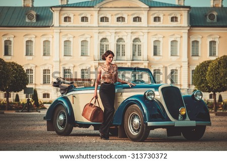 Beautiful lady with bag near classic convertible - stock photo