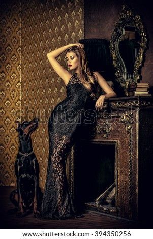 Beautiful lady with her dog in a room with luxurious classic interior. Fashion. - stock photo