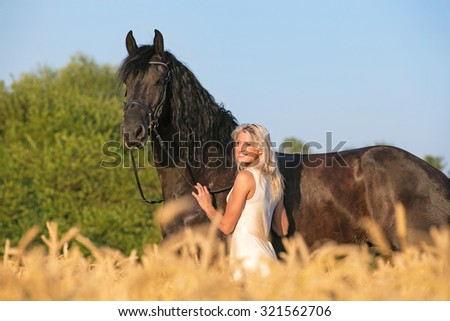 Beautiful lady with her horse on rye field background.