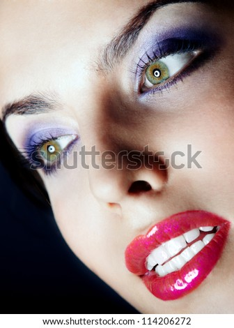 Beautiful lady with perfect dramatic makeup on a dark background