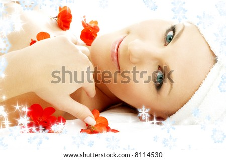 beautiful lady with red flower petals and snowflakes in spa - stock photo