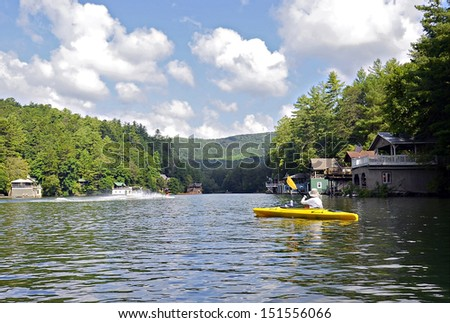 Beautiful lake area with people skiing and a woman on a kayak. - stock photo