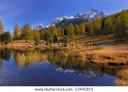Beautiful lake in autumn with reflections of a mountain - stock photo
