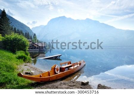 Beautiful lake in the Austrian Alps with a wooden boat in the morning
