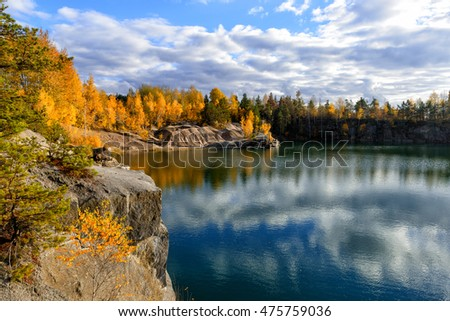 Beautiful lake in the fall time with colorful trees on a rocky shore
