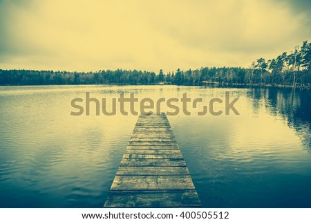 Beautiful lake landscape with romantic wooden pier or wooden jetty over, calm water surface, vintage photo - stock photo