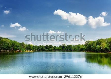 Beautiful lake nestled among rainforest in Cambodia under blue sky with white clouds. Cambodia is a popular tourist destination of Asia. - stock photo